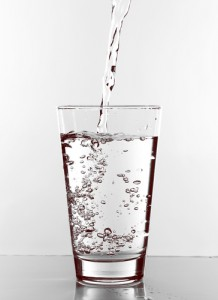 Glass of water with water being poured in