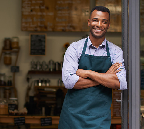Image of young Black business owner wearing an apron and standing in shop doorway.