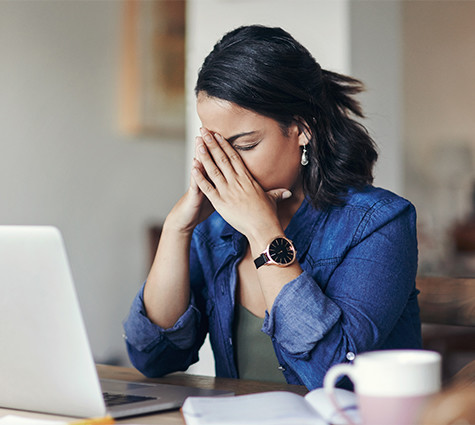 Image of stressed young female business owner sitting at her computer with hands on face
