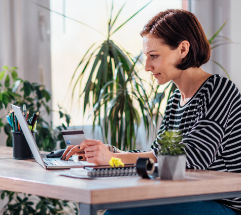 Image of woman looking at computer and paying something with her credit card