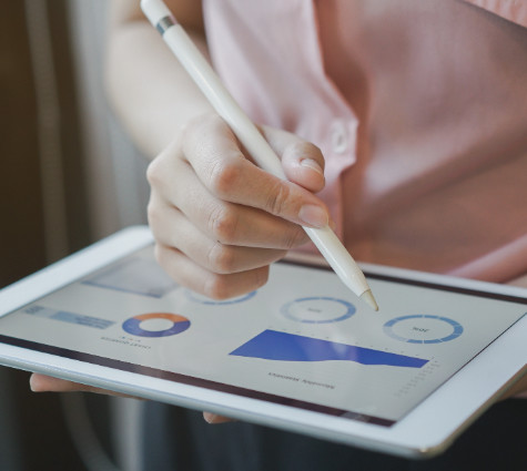 Image of woman holding her tablet and looking at business analytics.