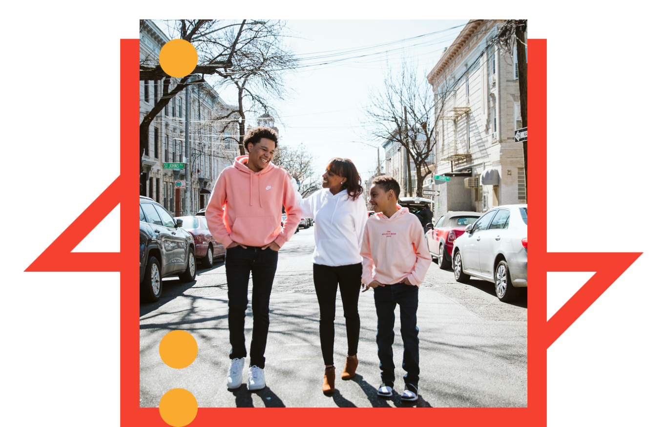 Nashira Lynton walking with her two sons in a neighborhood in New York